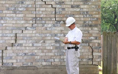 Construction worker analysing house foundation damage