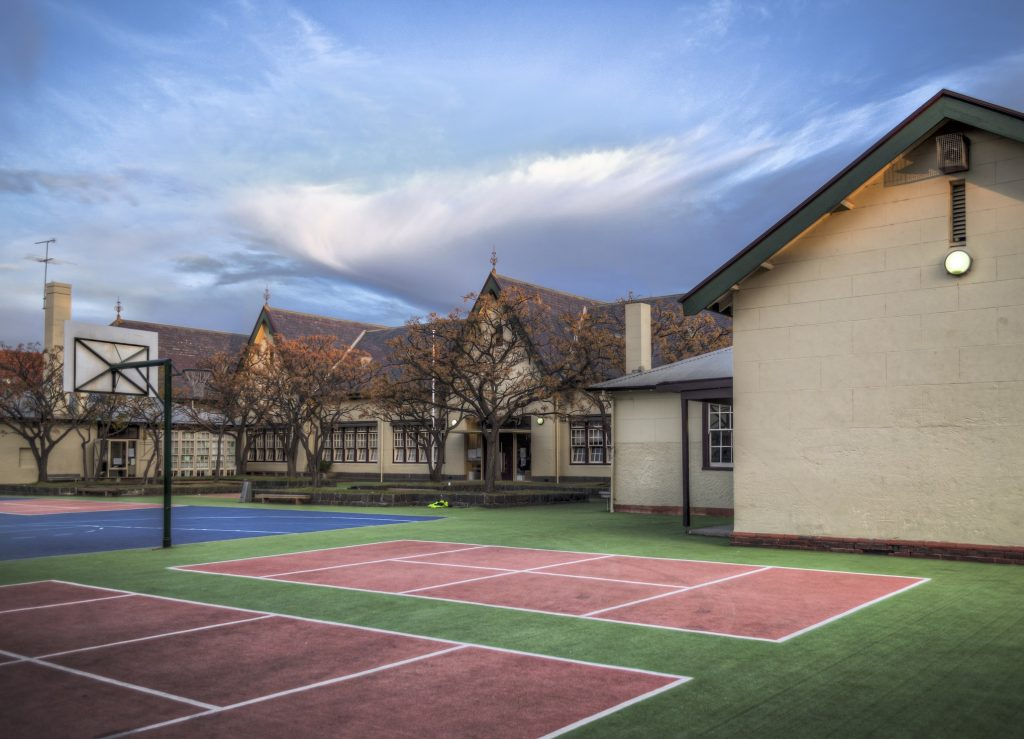 School Buildings and Sports Field Public school buildings and playground with synthetic turf and game courts - Melbourne, Australia.