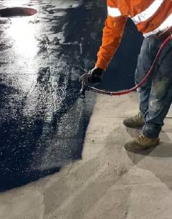 Mainmark technician spraying coating on concrete floor